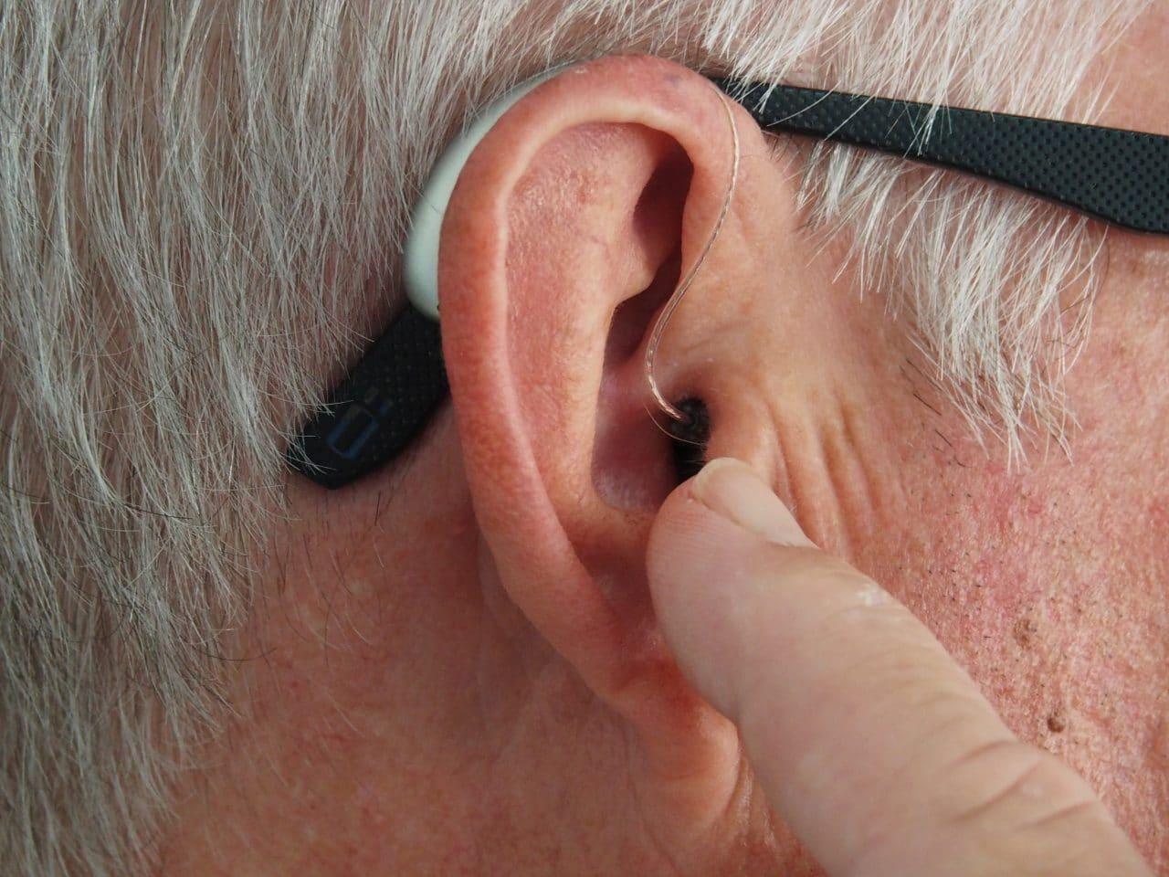 Man points at his hearing aid.