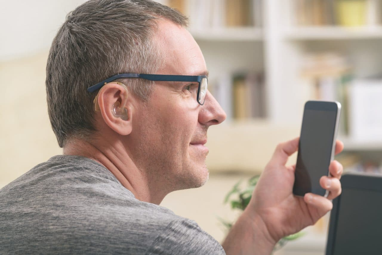 Man with hearing aid on smartphone
